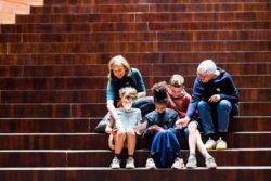 Oma, dochter en kleinkinderen op de trap van MoMu