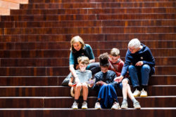 A family sitting on the stairs of MoMu