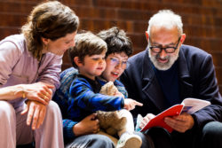 Grandpa, his daugther and the children sitting on the stairs of MoMu looking into a book