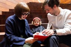 mama, papa en zoontje op trap in MoMu met een zoektochtje in de hand