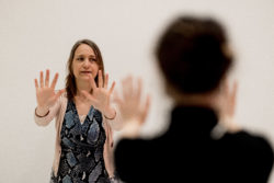 two persons facing each other practising qigong, arms stretched, hands standing, fingers spread