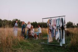 clothes rack with dresses made out of shirts and models that wear shirt dresses in an outdoor prairie setting