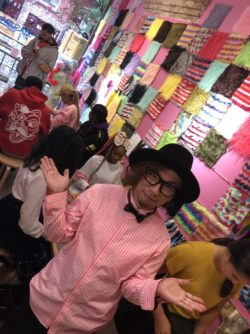 Sabastian Masuda met zwarte hoed en strik tussen kleurrijk imitatiebont