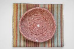 Coaster in roughly woven textile in a variety of colours with a handmade burgundy basket on it.