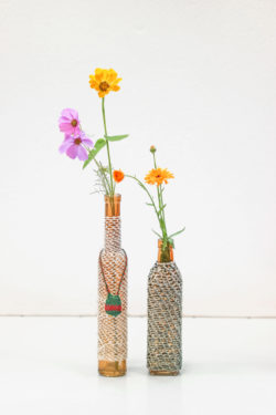 Two bottles wrapped in a fabric made with the looping technique. The bottles have flowers in them.