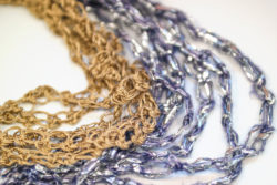 Detail of two necklaces in purple, silver and gold made with the Solomon's knot.