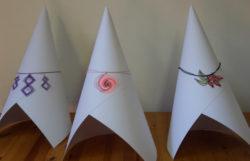 drie verschillende juweeltjes gemaakt van kloskanten tentoongesteld op een opgerold papier