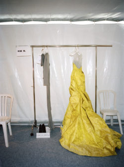 Clothing rack with a yellow dress on it.