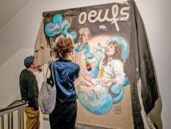 Twee bezoekers bekijken een kunstwerk in de tentoonstelling.