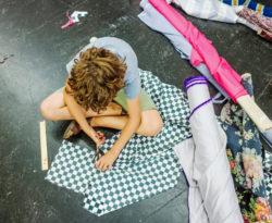 Kind zit op grond en knipt in een groot stuk zwart wit geruit textiel dat ook op de grond ligt.
