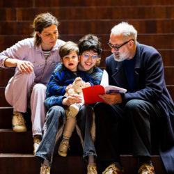 familie op trap kijkend in een boekje