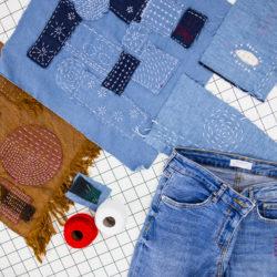 jeans-, okerkleurige stof en detail van jeansbroek, alle bewerkt met boro en sashiko; bolletje rood en wit sashiko garen en setje naalden