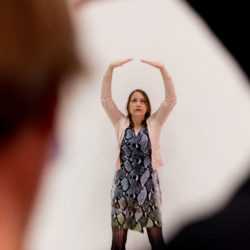 person striking a qigong pose, arms above the head like a crown