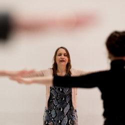twee personen tegenover elkaar die met armen zijlings gestrekt een qigong oefening doen