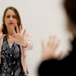 person standing, arms stretched in front , hands standing, fingers spread