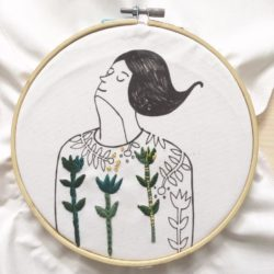 drawing of female figure in embroidery hoop with colourful embroidered details