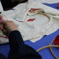 Women's hands embroidering a white fabric.