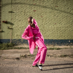 Woman in a fuchsia suit strikes a dynamic pose.