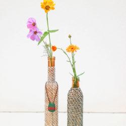 Foto van twee flessen, omhuld in een jasje, geknoopt in looping techniek. De flessen zijn gevuld met gekleurde bloemen.