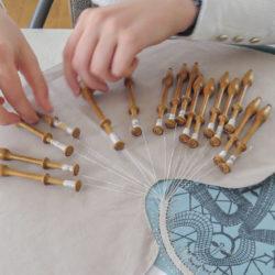 handen die kantslagen uitvoeren met klosjes op een motief