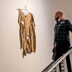 """A visitor looks an artwork in the exhibition """"Soft? Tactile Dialogues""""."""