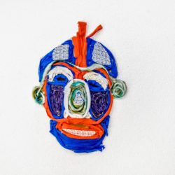 A mask depicting a human face in red and blue.