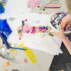 Child embellishes a female silhouette on paper with various types of textile and small sequin to achieve a 3D design.