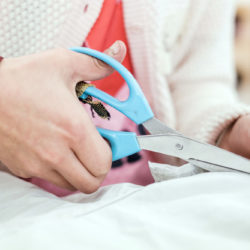 A child's hand with a big pair of blue scissors cuts into a piece of textile.