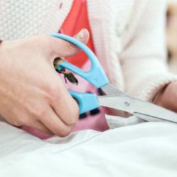 Een kinderhand met grote blauwe schaar knipt in een stuk textiel.