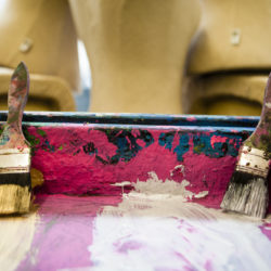 A variety of paint brushes in a wooden paint tray with pink paint in it.