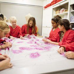 Kinderen met een rode schort zitten samen aan tafel en bekijken een groot stuk textiel dat op de tafel ligt.