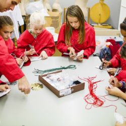 Children in red aprons are seated at a table and cut into pieces of textile and work with various materials.