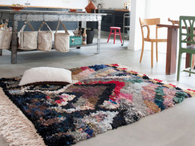 A colourful carpet lies on a concrete floor in a kitchen.