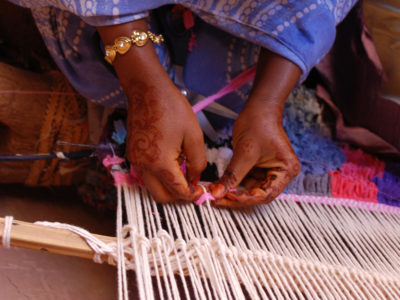 Two hands weaving a tapestry.