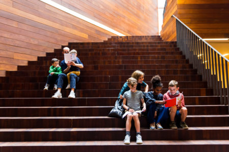 adults and children sitting on the stairs of MoMu