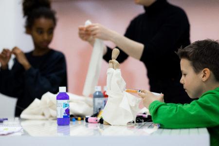 Children working on a little dress on a little doll