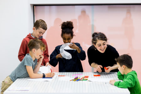 different children working on a collar in paper by cutting in a peace of paper