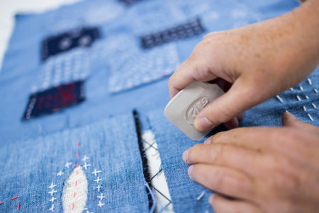 jeans fabric with boro and sashiko techniques, hands  using tailor's chalk