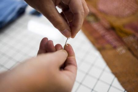 hand that threads a sashiko knot
