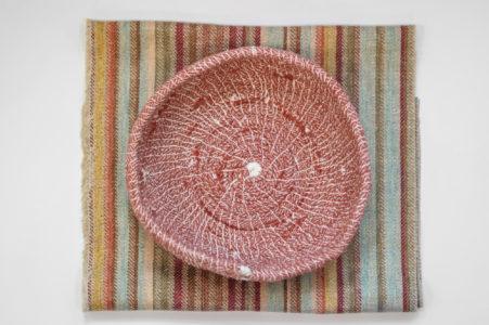 Onderlegger in grof geweven textiel in verschillende kleuren met daarop een handgemaakte bordeaux mandje in bovenaanzicht.