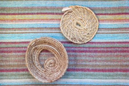 Two baskets made with the coiling technique, placed on a roughly woven piece of textile.