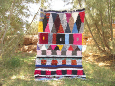 A colourful tapestry with squares and triangels hanging from a line.