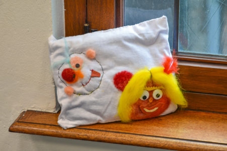 A pillow with colourful embroidery is positioned in a windowsill.