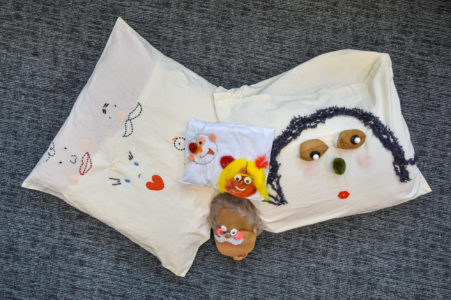 Two cushions embroiderd with colorful portraits are positioned on the floor.