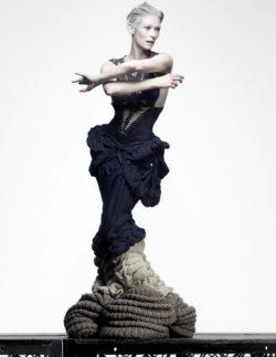 Affichebeeld voor de tentoonstelling ONTRAFEL. Actrice Tilda Swinton staat op een platform in een dramatische jurk uit tricot.