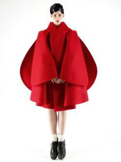Affichebeeld voor de tentoonstelling Game Changers. Model Monika Sawicka draagt een rode architecturale mantel van Comme des Garçons.
