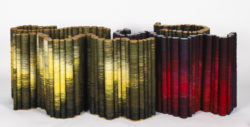 Tubular structures in wood that are wrapped in thread in multi-colour gradations.