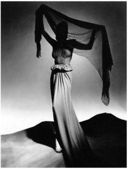 Een zwart-wit foto uit de jaren veertig door fotograaf George Platt Lynes. Het model draagt een geplooide creatie van de ontwerper Madame Grès.