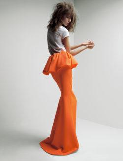 Affichebeeld voor de tentoonstelling MoMu Nu. Het model draagt een wit-shirt met een oranje rok met een peplum. Het silhouet is van de lente-zomer collectie 201 van het huis Jil Sander.