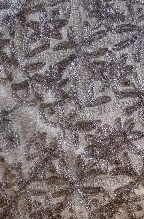 Detail of fabric with embroidered flowers in silver.
